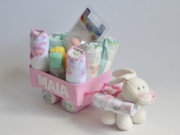 Canastilla de pañales personalizada con forma de carrito con regalitos en su interior para recién nacido